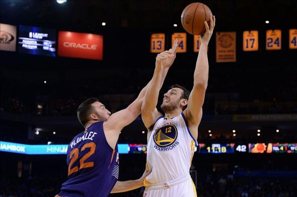 December 27, 2013; Oakland, CA, USA; Golden State Warriors center Andrew Bogut (12) shoots the ball against Phoenix Suns center Miles Plumlee (22) during the third quarter at Oracle Arena. The Warriors defeated the Suns 115-86. Mandatory Credit: Kyle Terada-USA TODAY Sports