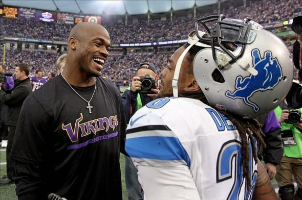 Dec 29, 2013; Minneapolis, MN, USA; Minnesota Vikings running back Adrian Peterson (28) laughs with Detroit Lions safety Louis Delmas (26) following the game at Mall of America Field at H.H.H. Metrodome. The Vikings defeated the Lions 14-13. Mandatory Credit: Brace Hemmelgarn-USA TODAY Sports