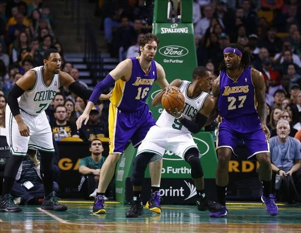 Jan 17, 2014; Boston, MA, USA; Boston Celtics point guard Rajon Rondo (9) works the ball against Los Angeles Lakers center Pau Gasol (16) and center Jordan Hill (27) in the first quarter at TD Garden. Mandatory Credit: David Butler II-USA TODAY Sports