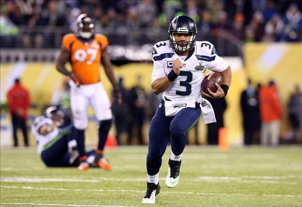 Feb 2, 2014; East Rutherford, NJ, USA; Seattle Seahawks quarterback Russell Wilson (3) runs against the Denver Broncos during the fourth quarter in Super Bowl XLVIII at MetLife Stadium. Mandatory Credit: Matthew Emmons-USA TODAY Sports