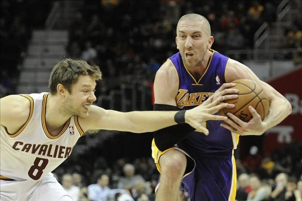 Feb 5, 2014; Cleveland, OH, USA; Los Angeles Lakers point guard Steve Blake (right) dribbles the ball as Cleveland Cavaliers shooting guard Matthew Dellavedova defends in the third quarter at Quicken Loans Arena. Mandatory Credit: David Richard-USA TODAY Sports