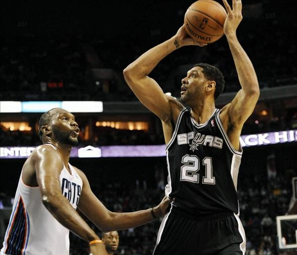 Feb 8, 2014; Charlotte, NC, USA; San Antonio Spurs forward Tim Duncan (21) looks to pass as he is defended by Charlotte Bobcats center Al Jefferson (25) during the second half of the game at Time Warner Cable Arena. Spurs win 104-100. Mandatory Credit: Sam Sharpe-USA TODAY Sports