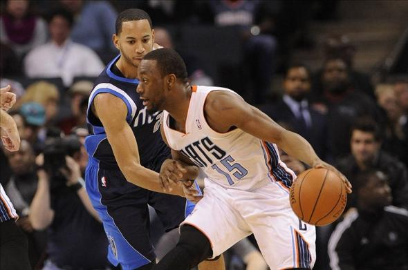 Feb 11, 2014; Charlotte, NC, USA; Charlotte Bobcats guard Kemba Walker (15) dribbles the ball around Dallas Maverick guard Devin Harris (20) during the first half at Time Warner Cable Arena. Mandatory Credit: Sam Sharpe-USA TODAY Sports