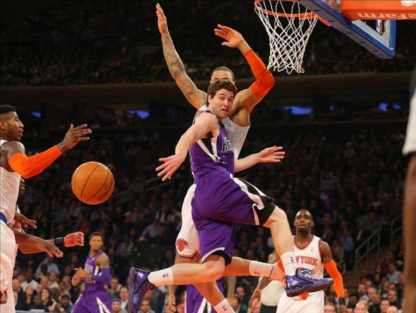Feb 12, 2014; New York, NY, USA; Sacramento Kings point guard Jimmer Fredette (7) passes the ball back outside as his path to the basket is cut off by New York Knicks center Tyson Chandler (6) during the first half at Madison Square Garden. Mandatory Credit: Jim O