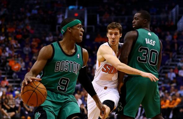 Feb 19, 2014; Phoenix, AZ, USA; Boston Celtics guard Rajon Rondo (9) controls the ball as forward Brandon Bass (30) blocks Phoenix Suns guard Goran Dragic in the first quarter at US Airways Center. Mandatory Credit: Mark J. Rebilas-USA TODAY Sports