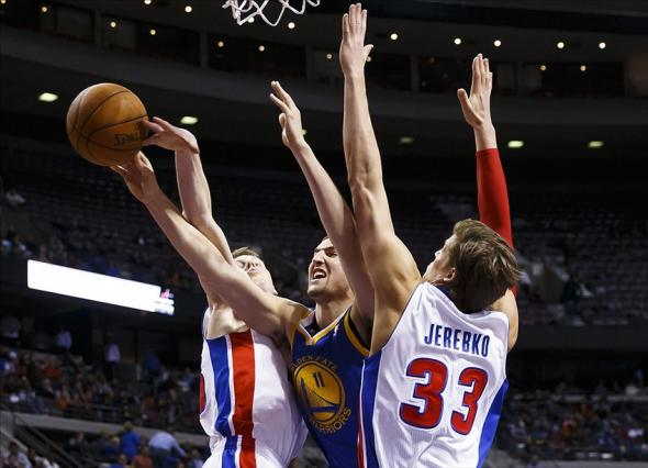 Feb 24, 2014; Auburn Hills, MI, USA; Golden State Warriors shooting guard Klay Thompson (11) shoots the ball as Detroit Pistons small forward Kyle Singler (L) and power forward Jonas Jerebko (33) defend at The Palace of Auburn Hills. Mandatory Credit: Rick Osentoski-USA TODAY Sports