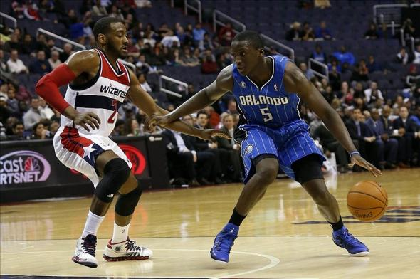 Feb 25, 2014; Washington, DC, USA; Orlando Magic shooting guard Victor Oladipo (5) dribbles the ball as Washington Wizards point guard John Wall (2) defends in the fourth quarter at Verizon Center. The Wizards won 115-106. Mandatory Credit: Geoff Burke-USA TODAY Sports
