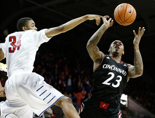 Feb 8, 2014; Dallas, TX, USA; Southern Methodist Mustangs forward Ben Moore (34) blocks a shot by Cincinnati Bearcats guard Sean Kilpatrick (23) during the first half of a men