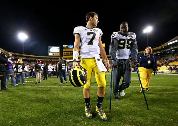 Dec 28, 2013; Tempe, AZ, USA; Michigan Wolverines quarterback Shane Morris (7) walks off the field with injured quarterback Devin Gardner (98) following the game against the Kansas State Wildcats during the Buffalo Wild Wings Bowl at Sun Devil Stadium. Kansas State defeated Michigan 31-14. Mandatory Credit: Mark J. Rebilas-USA TODAY Sports