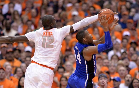 Feb 1, 2014; Syracuse, NY, USA; Duke Blue Devils guard Rasheed Sulaimon (14) shoots the ball with Syracuse Orange center Baye-Moussa Keita (12) defending during the second half of a game at the at Carrier Dome. Syracuse won the game 91-89. Mandatory Credit: Mark Konezny-USA TODAY Sports