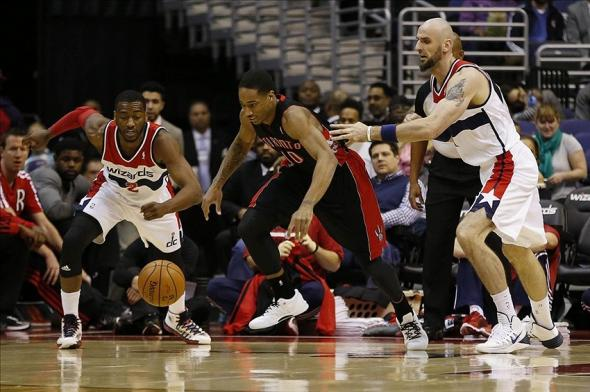Feb 18, 2014; Washington, DC, USA; Washington Wizards point guard John Wall (2) battles for the ball with Toronto Raptors shooting guard DeMar DeRozan (10) in the first quarter at Verizon Center. Mandatory Credit: Geoff Burke-USA TODAY Sports