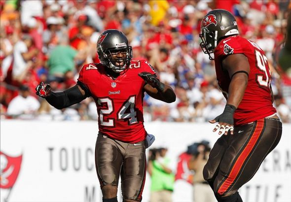 Dec 8, 2013; Tampa, FL, USA; Tampa Bay Buccaneers cornerback Darrelle Revis (24) is congratulated by defensive tackle Gerald McCoy (93) after he made a sack against the Buffalo Bills during the first half at Raymond James Stadium. Mandatory Credit: Kim Klement-USA TODAY Sports