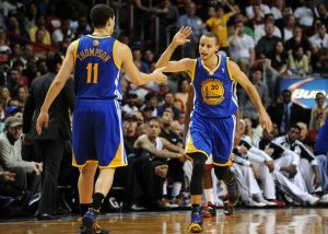 Jan 2, 2014; Miami, FL, USA; Golden State Warriors point guard Stephen Curry (right) greets teammate Golden State Warriors shooting guard Klay Thompson (left) during the second half against the Miami Heat at American Airlines Arena. Mandatory Credit: Steve Mitchell-USA TODAY Sports