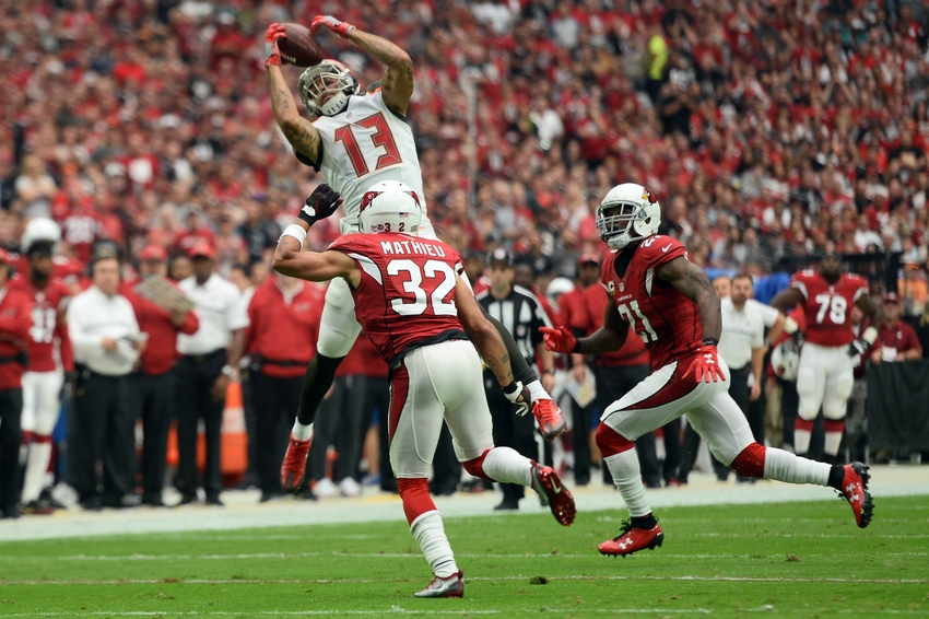 Sep 18, 2016; Glendale, AZ, USA; Tampa Bay Buccaneers wide receiver Mike Evans (13) makes a catch against Arizona Cardinals free safety Tyrann Mathieu (32) and Arizona Cardinals cornerback Patrick Peterson (21) during the first half at University of Phoenix Stadium. Mandatory Credit: Joe Camporeale-USA TODAY Sports