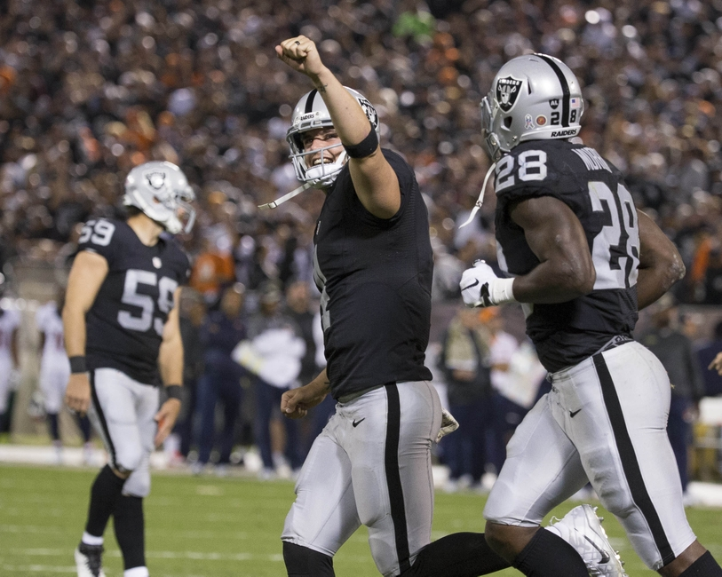 Nov 6, 2016; Oakland, CA, USA; Oakland Raiders quarterback Derek Carr (4) celebrates after a touchdown in the second quarter against the Denver Broncos at Oakland Coliseum. Mandatory Credit: Neville E. Guard-USA TODAY Sports