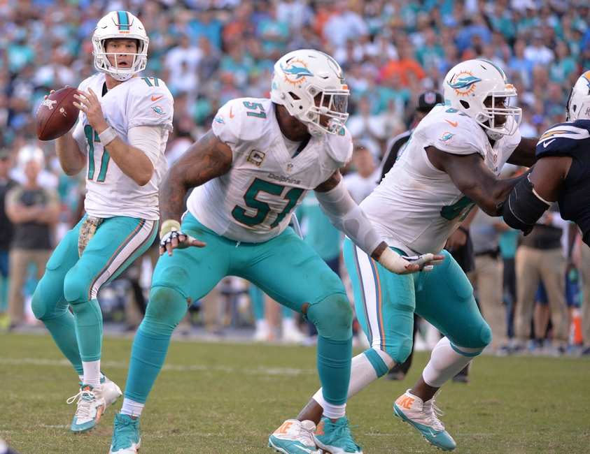 Nov 13, 2016; San Diego, CA, USA; Miami Dolphins quarterback Ryan Tannehill (17) looks to pass while protected by center Mike Pouncey (51) and offensive guard Laremy Tunsil (67) during the second half against the San Diego Chargers at Qualcomm Stadium. Miami won 31-24. Mandatory Credit: Orlando Ramirez-USA TODAY Sports