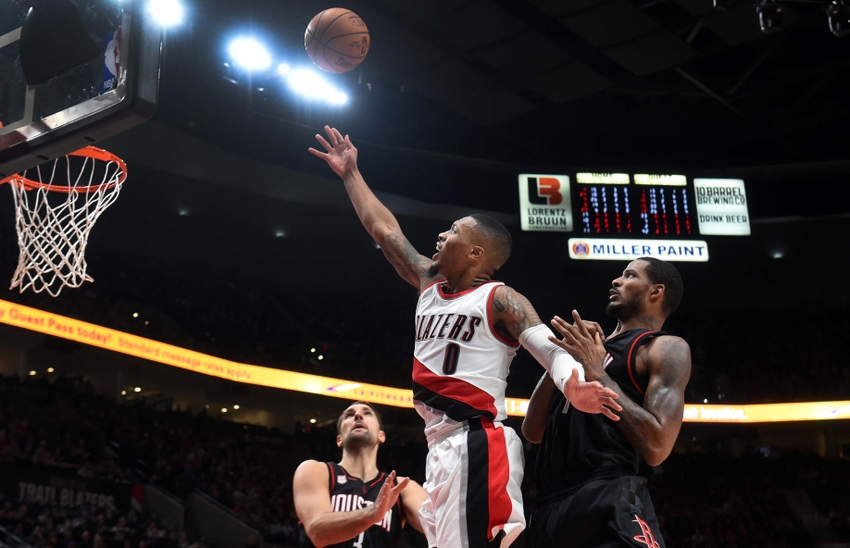 Nov 27, 2016; Portland, OR, USA; Portland Trail Blazers guard Damian Lillard (0) drives to the basket on Houston Rockets forward Ryan Anderson (3) and forward Trevor Ariza (1) during the fourth quarter of the game at the Moda Center at the Rose Quarter. The Rockets won 130-114. Mandatory Credit: Steve Dykes-USA TODAY Sports