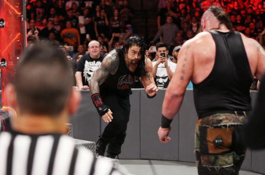Roman Reigns hits a Spear on Braun Strowman.