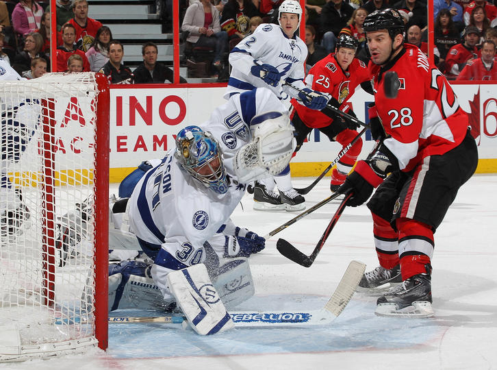 OTTAWA, CANADA - DECEMBER 5: Dwayne Roloson #30 of the Tampa Bay Lightning falls across his crease after deflecting the puck away from Zenon Konopka #28 of the Ottawa Senators at Scotiabank Place on December 5, 2011 in Ottawa, Ontario, Canada. (Photo by Andre Ringuette/NHLI via Getty Images)