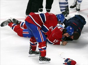 Oct 1, 2013; Montreal, Quebec, CAN; Montreal Canadiens right wing George Parros (15) gets medical assistance as teammate Brandon Prust (8) looks on during the third period against Toronto Maple Leafs at Bell Centre. Mandatory Credit: Jean-Yves Ahern-USA TODAY Sports