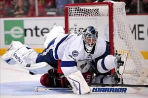 Oct 5, 2013; Chicago, IL, USA; Tampa Bay Lightning goalie Ben Bishop (30) lands on top of Chicago Blackhawks left wing Brandon Saad (20) during the second period at the United Center. Mandatory Credit: Rob Grabowski-USA TODAY Sports