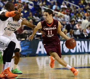 Mar 12, 2014; Greensboro, NC, USA; Virginia Tech Hokies guard Devin Wilson (11) moves the ball around past Miami Hurricanes center Tonye Jekiri (23) and guard Garrius Adams (25) during the first round of the ACC Tournament at Greensboro Coliseum. Mandatory Credit: John David Mercer-USA TODAY Sports