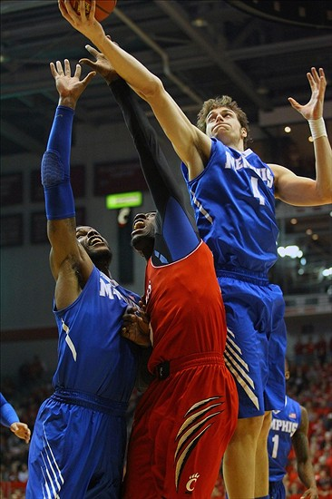 Mar 6, 2014; Cincinnati, OH, USA; Memphis Tigers forward Austin Nichols (4) rebounds a shot over Cincinnati Bearcats forward Justin Jackson (5) during the first half of the game at Fifth Third Arena. Mandatory Credit: Rob Leifheit-USA TODAY Sports