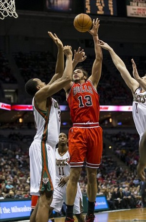 Dec 13, 2013; Milwaukee, WI, USA; Chicago Bulls center Joakim Noah (13) shoots against Milwaukee Bucks forward John Henson (31) during the second quarter at BMO Harris Bradley Center. Mandatory Credit: Jeff Hanisch-USA TODAY Sports