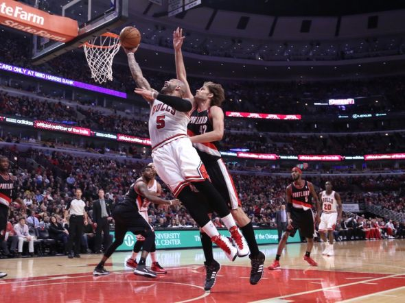 Mar 28, 2014; Chicago, IL, USA; Chicago Bulls forward Carlos Boozer (5) scores past Portland Trail Blazers center Robin Lopez (42) during the second half at the United Center. Portland won 91-74. Mandatory Credit: Dennis Wierzbicki-USA TODAY Sports