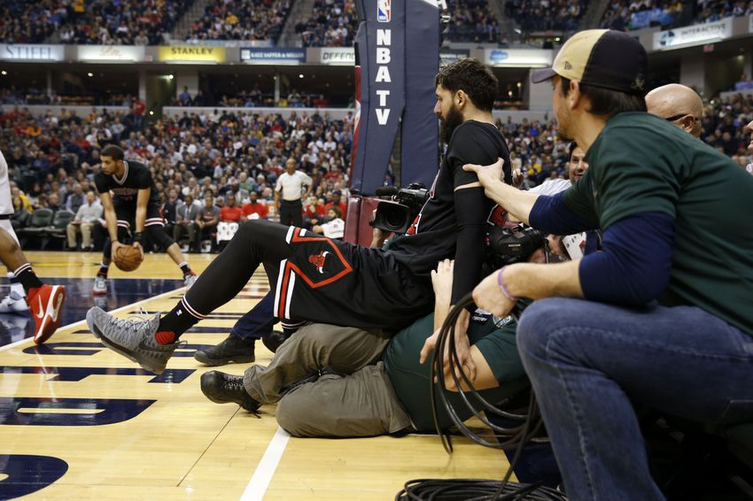Dec 30, 2016; Indianapolis, IN, USA;  Chicago Bulls forward Nikola Mirotic (44) falls out of bounds and lands a videographer during a game against the Indiana Pacers at Bankers Life Fieldhouse. Mandatory Credit: Brian Spurlock-USA TODAY Sports
