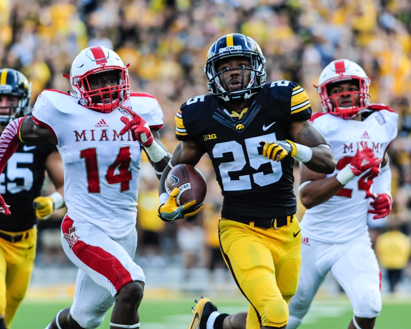 Sep 3, 2016; Iowa City, IA, USA; Iowa Hawkeyes running back Akrum Wadley (25) is chased by Miami (Oh) Redhawks defensive back Tony Reid (14) and defensive back Heath Harding (24) during the fourth quarter at Kinnick Stadium. The Hawkeyes won 45-21. Mandatory Credit: Jeffrey Becker-USA TODAY Sports