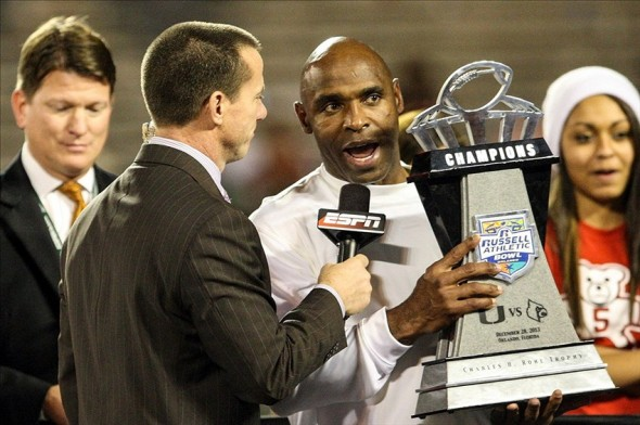 Dec 28, 2013; Orlando, FL, USA; Louisville Cardinals head coach Charlie Strong is presented with the Russell Athletic Bowl trophy after defeating the Miami Hurricanes at Florida Citrus Bowl Stadium. Mandatory Credit: Rob Foldy-USA TODAY Sports