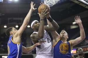 DeMarcus Cousins drives on David Lee and Klay Thompson
