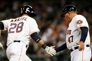 A Houston Astros Player Slaps Hands With a Base Coach