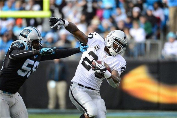 Dec 22, 2012; Charlotte, NC, USA; Oakland Raiders running back Darren McFadden (20) runs as Carolina Panthers outside linebacker Thomas Davis (58) defends in the first quarter at Bank of America Stadium. Mandatory Credit: Bob Donnan-USA TODAY Sports