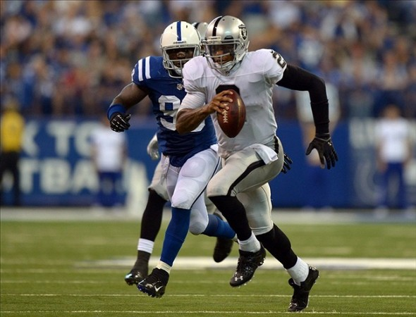 Sep 8, 2013; Indianapolis, IN, USA; Oakland Raiders quarterback Terrelle Pryor (2) scrambles from Indianapolis Colts linebacker Robert Mathis (98) at Lucas Oil Stadium. The Colts defeated the Raiders 24-21. Mandatory Credit: Kirby Lee-USA TODAY Sports