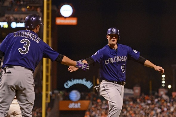 September 9, 2013; San Francisco, CA, USA; Colorado Rockies second baseman D.J. LeMahieu (9) is congratulated by right fielder Michael Cuddyer (3) for scoring on a RBI-single by shortstop Troy Tulowitzki (2, not pictured) against the San Francisco Giants during the third inning at AT