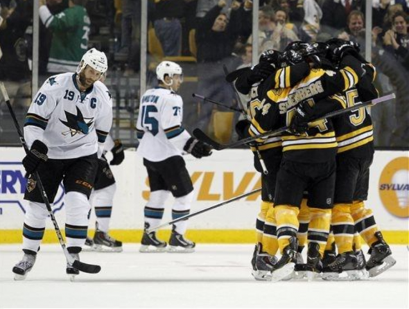San Jose Sharks center Joe Thornton (19), left, looks down as the Boston Bruins celebrate the game-winning goal during the third period of an NHL hockey game Thursday, Oct. 24, 2013, in Boston. The Bruins won 2-1. (AP Photo/Mary Schwalm)