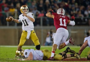 Nov 30, 2013; Stanford, CA, USA; Notre Dame Fighting Irish quarterback Tommy Rees (11) throws a pass as Stanford Cardinal linebacker Shayne Skov (11) pressures in the second quarter at Stanford Stadium. Mandatory Credit: Matt Cashore-USA TODAY Sports