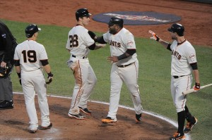 Oct 22, 2012; San Francisco, CA, USA; San Francisco Giants second baseman Marco Scutaro (19), catcher Buster Posey (28), and third baseman Pablo Sandoval (second from right) celebrate after all scored on a two-RBI double by right fielder Hunter Pence (not pictured) as first baseman Brandon Belt (far right) looks on during the third inning of game seven of the 2012 NLCS against the St. Louis Cardinals at AT