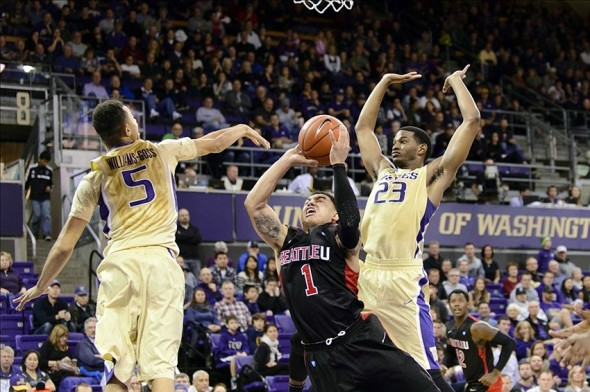 Nov 10, 2013; Seattle, WA, USA; Seattle Redhawks guard Isiah Umipig (1) is fouled by Washington Huskies guard C.J. Wilcox (23) during a layup in the 2nd half at Alaska Airlines Arena. Washington defeated Seattle 88-78. Mandatory Credit: Steven Bisig-USA TODAY Sports