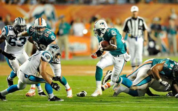 Aug.19, 2011; Miami, FL, USA; Miami Dolphins running back Kory Sheets (23) runs past the Carolina Panthers defense during the third quarter against the Carolina Panthers at Sun Life Stadium. Mandatory Credit: Steve Mitchell-USA TODAY Sports