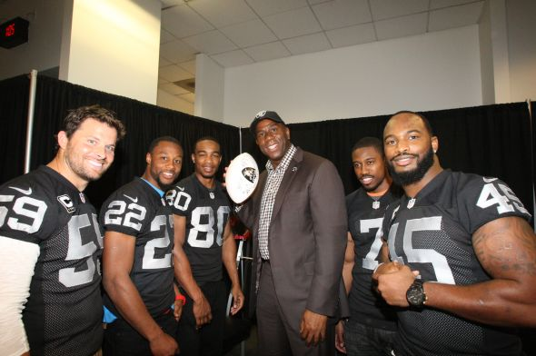 Jon Condo, Taiwan Jones, Rod Streater, Marquette King and Marcel Reece surround a Raider capped Magic Johnson during We Day at Oracle Arena. (TONY GONZALES/raiders.com)