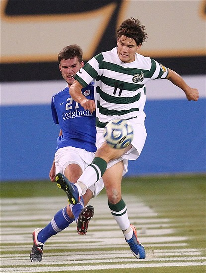 Dec 09, 2011; Hoover, AL, USA; UNC Charlotte 49ers forward Giuseppe Gentile (11) kicks the ball as Creighton Bluejays defender Jace Peters (21) defends during the finals of the NCAA Division I men