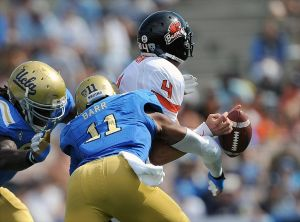 Sept. 22, 2012; Pasadena, CA, USA; UCLA Bruins defensive end Owamagbe Odighizuwa (94) and linebacker Anthony Barr (11) sack Oregon State Beavers quarterback Sean Mannion (4) and force a fumble in the third quarter of the game at the Rose Bowl. Oregon State won 27-20. Mandatory Credit: Jayne Kamin-Oncea-USA TODAY Sports
