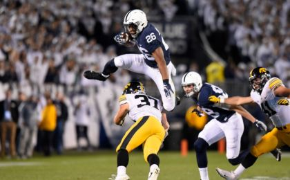 Nov 5, 2016; University Park, PA, USA; Penn State Nittany Lions running back Saquon Barkley (26) leaps over Iowa Hawkeyes defensive back Brandon Snyder (37) during the first quarter at Beaver Stadium. Mandatory Credit: Rich Barnes-USA TODAY Sports