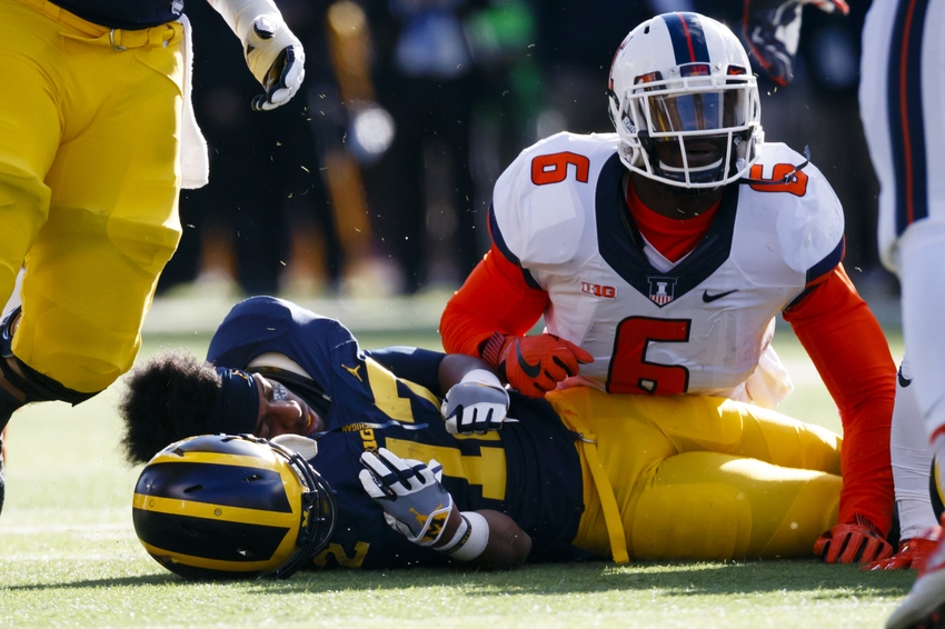 Oct 22, 2016; Ann Arbor, MI, USA; Michigan Wolverines running back Chris Evans (12) loose his helmet after he is tackled by Illinois Fighting Illini defensive lineman Carroll Phillips (6) in the first half at Michigan Stadium. Mandatory Credit: Rick Osentoski-USA TODAY Sports