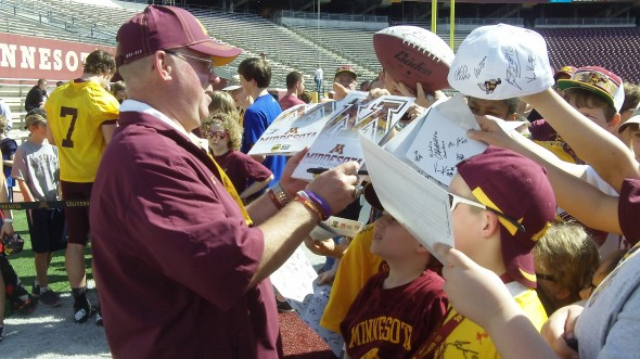 Minnesota head football coach Jerry Kill signs autographs for fans after the 2013 Spring Game. Quarterback Mitch Leidner can also be seen doing the same (No. 7 in gold).