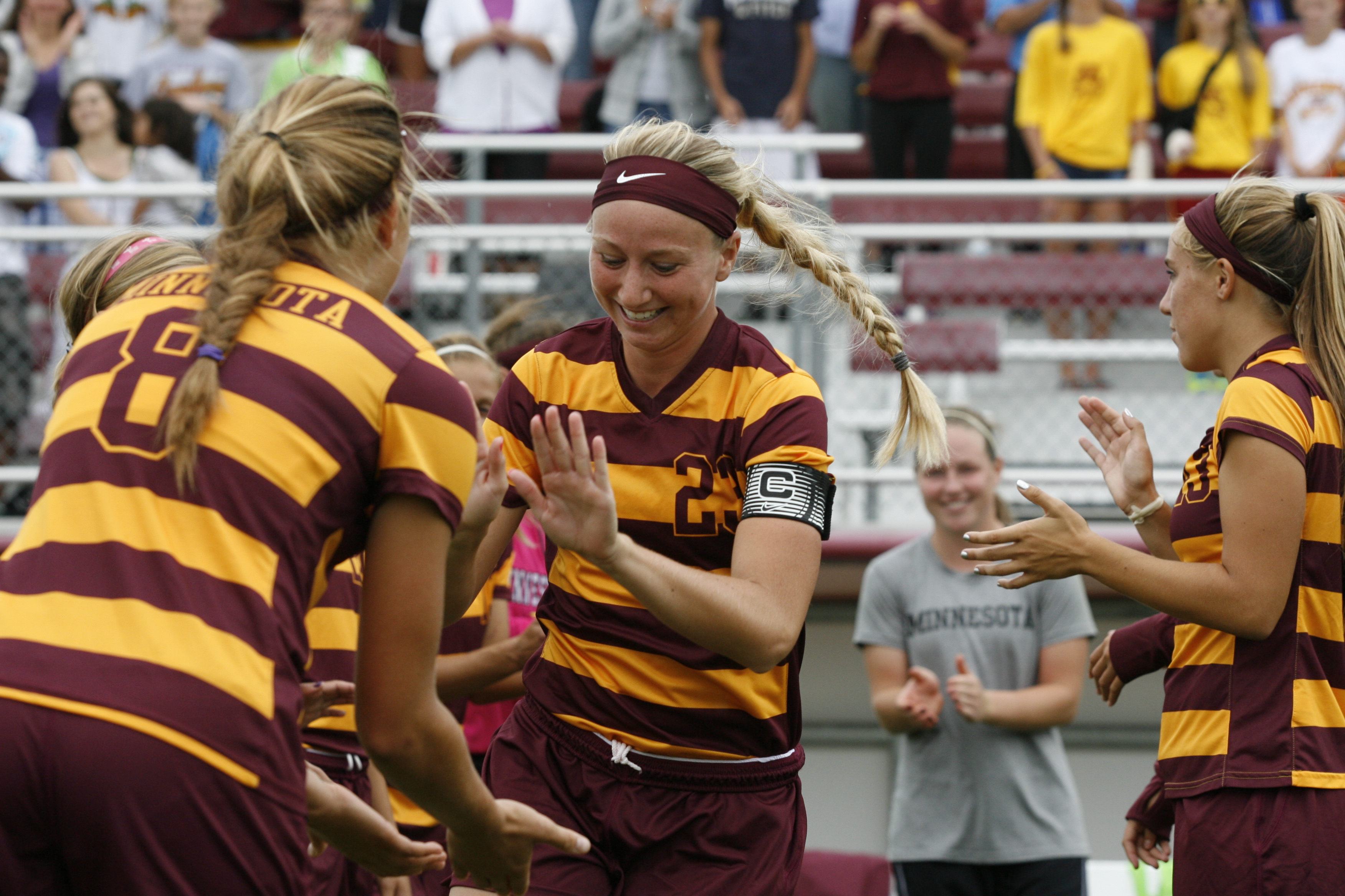 University of Minnesota senior captain MacKenzie Misel running past teammates at Elizabeth Lyle Robbie Stadium.
