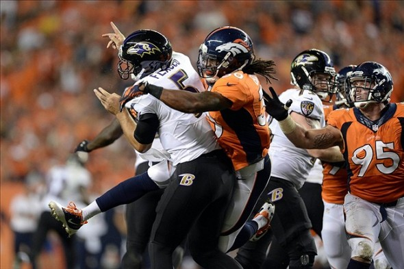 Sep 5, 2013; Denver, CO, USA; Denver Broncos strong safety David Bruton (30) hurries Baltimore Ravens quarterback Joe Flacco (5) in the third quarter at Sports Authority Field at Mile High. The Broncos defeated the Ravens 49-27. Mandatory Credit: Ron Chenoy-USA TODAY Sports